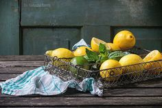 Heap of whole and sliced lemons and limes with mint in vintage metal grid box over old wooden table with turquoise wooden background. Dark rustic style. lemon lime lemons fresh limes wood food citrus color wooden table juicy fruit ingredient background green healthy yellow ripe summer juice organic tropical vitamin nobody diet cut raw natural bowl agriculture cooking slice lemonade mojito squeezed rustic kitchen vintage turquoise towel textile