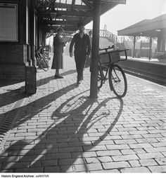A general view along a platform of Sheringham Station in Norfolk, showing a bicycle leaning against a canopy post, passengers waiting for their trains and the opposite platform and bridge over the tracks in the background. Date 1959 Photographer: John Gay Horse Drawn, Sun Shade, Light And Shadow, Norfolk, Canopy, Transportation, Sidewalk, Gay, England