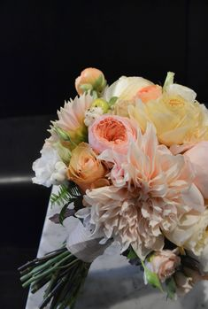 Bridal bouquet including cafe au lait dahlias, garden roses, sahara rose, spray rose and ranunculus. Lush round classic bouquet with faded fall colors. Gramercy Park Hotel Terrace Wedding. Rosehip Social Floral Design.