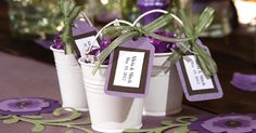 """These tin pail favors come with white ribbon and """"Thank You"""" tags — just add a little candy and you're done! Or, if you want more of a unique look, you can create a personalized tag and swap out the white ribbon for a ribbon color that coordinates with your wedding theme. What You'll Need: 3-ct. Packs of Tin Pail Favors Heavy Card Stock Paper Tag Template Hole Puncher Ribbon Craft Glue Scissors Candy, Nuts, or Mints Easy Step-By-Step Directions:..."""
