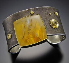 Jeff and Susan Wise : Elegant cuff in oxidized sterling silver with a translucent brazilian picture quartz set in 18k & 22k gold. An aceent stone of faceted Mali garnet is et in 18k gold.