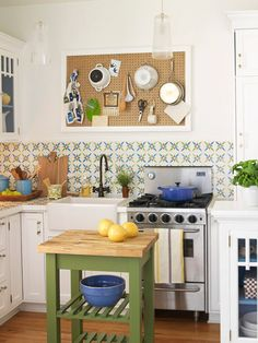 While not a fan of the Julia Child-inspired peg board (I'd hang a print...), I do love the tile and green island.