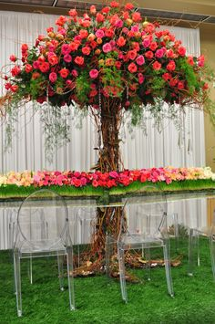 8 foot tall sculpted floral tree growing through a lucite table with floral runner.