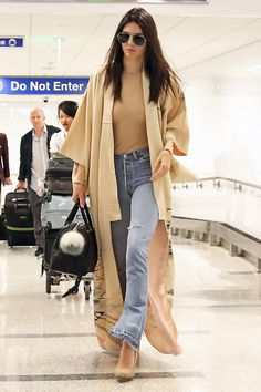 Jenner goes casual chic for her flight from London to Los Angeles wearing a tan bodysuit and distressed flares topped with a camel duster jacket.    - HarpersBAZAAR.com