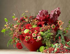 This massive holiday arrangement from Avant Garden features a wide array of elements, including Dutch fall hydrangea, crab apple branches, Rothschild vanda orchids, dahlia, Madrone berries, blue juniper, amaryllis, ranunculi, horse apples, cocculus, nandina berries, Jesus blood vine, diplocyclos, and chokecherry.