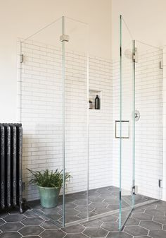 modern bath in historic home: dark cement hex tiles with white grout and white subway tiles with gray grout, linear drain allows the floor to be contiguous