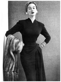 Model is wearing elegant slim sheath draped artfully around the hip, photo by John French, 1950's