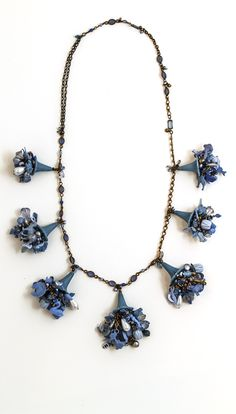 Robin Ayres – This necklace started as a charm bracelet with smokey blue plastic dog charms from my favorite antique store. Now each charm anchors a flower of vintage beads, other plastic charms and vintage rhinestones