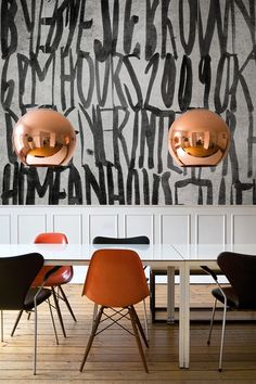 A mismatched (yet color coordinated) set of mid-century modern chairs become a quirky casual collection when assembled along a clean white work surface. Handwritten oversized text becomes a graphic pattern on wall surfaces, while copper pendant light fixtures provide pop.