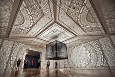 Intersections by Anila Quayyum Agha. Laser-cut black lacquer wood cube suspended from the ceiling and lit with a single light bulb that casts breathtaking 32-feet-by-34-feet shadows to create instant architecture in an otherwise empty room