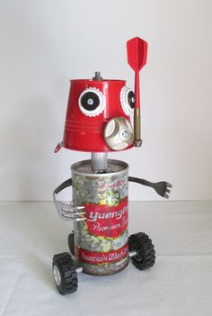 SUDZ is a very unique found object sculpture made from junk objects that include a vintage Yuengling beer can, beer bottle caps, a red dart, fishing reel part, miniature red metal bucket, pennies, forks, toy wheels, antique caster wheel, wire, circuit board, etc. This is a one of a kind piece of folk art that stands out and makes for a great conversation piece. Perfect for work, office, restaurants, home décor, art galleries, etc. It rolls back and forth to give it that robot like feel. SUDZ…