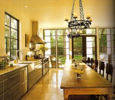 I love the warmth of this kitchen.  I think sometimes a kitchen can look cold with stainless steel and tile flooring.  The wood table really warms it up along with the chandelier.