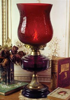 A frosted deco floral is illuminated upon crimson glass by the internal flame. The oil chamber is purple glass, believed by the Victorians to protect the home from harm''s way. Basin holds ozs of oil. Antique Lamps, Vintage Lamps, Victorian Gothic Decor, Hurricane Oil Lamps, Victorian Trading Company, Steampunk House, Red Cottage, Stained Glass Lamps, Purple Glass