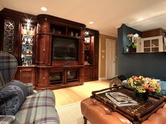 One wall in this living room is lined with a mahogany-stained entertainment center that features a large television. Display cases filled with knick knacks, bottles of liquor and statues are accented with cabinet display lighting for a decorative touch in the room.