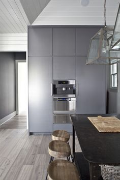 source: Heather A Wilson, Architect Modern, contemporary kitchen design with white tongue and groove walls & vaulted ceiling, gray modern cabinets with built-in espresso machine, metal center island and Wisteria Smart and Sleek Stools. Modern Grey Kitchen, Swedish Kitchen, Contemporary Kitchen Design, New Kitchen, Modern Contemporary, Studio Kitchen, Scandinavian House, Floor Design, House Design