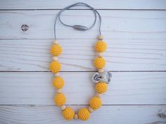 This crochet jewelry is a modern teething necklace made of mango crocheted beads and natural wood beads. This chewelry necklace is the perfect nursing necklace for keeping your little ones hands busy while nursing. The chewable necklace is the perfect teething accessory while babywearing. This fiddle necklace makes a great baby shower gift for a new mom. Check out all of our teething necklaces and DIY teething supplies at www.etsy.com/shop/kellymariesboutique