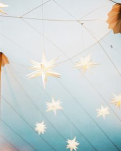 Skyline Tent Company helped the couple source about 20 affordable Moravian/Moroccan-inspired star pendants in two different sizes. The stars, clustered above the dance floor, tied together the reception's design.
