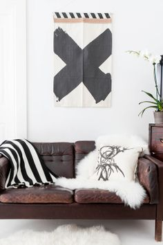 A wall hanging by Australian textile designer Pony Rider hangs above a vintage Danish sofa in Annabelle Kerslake's Australia home.