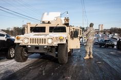 1-30-14.  National Guard Pfc. Josh Krunnker prepares to tow a car near Interstate 285 on Wednesday in Dunwoody, Ga. Georgia. The National Guard was sending military Humvees onto Atlanta's snarled freeway system in an attempt to move stranded school buses and get food and water to people. Georgia State Patrol troopers headed to schools where children were hunkered down early Wednesday after spending the night there.