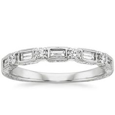 Introducing The Vintage Diamond Baguette Ring | Evocative of days gone by, this vintage inspired ring features sparkling diamond baguettes alternating with round diamonds and surrounded by delicate milgrain. The band is hand-engraved in a fanciful floral pattern on both the top and sides for additional appeal.  #BrilliantEarth