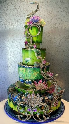 have your wedding cake decked out in vibrant green and blue with some floral designs - perfect peacock themed wedding