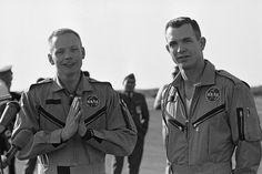 """Gemini 8 Command Pilot Neil Armstrong, left, presses his hands together in prayerful attitude as he and his co-pilot, David Scott, returned to scene of their blast-off, March 19, 1966, Cape Kennedy, Fla. Armstrong told a small welcoming group that they """"had a magnificent flight for the first seven hours and we were very pleased with the way it came out."""" The flight ended ahead of schedule after their docking with an unmanned Agena space vehicle."""