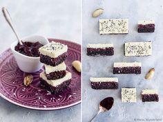 Ein gesunder Snack aus drei Schichten: Nuss-Boden mit Kakao, darauf Kirschmarmelade mit Chia-Samen und Kokosrapseln, bedeckt mit weißer Schokolade.