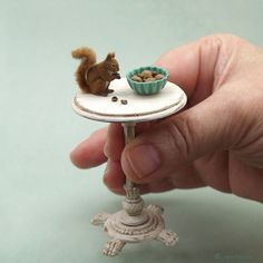 A dollhouse miniature European Red Squirrel  with bowl of nuts.  Ooak sculpture made from polymer clay & applied natural fiber coat.  Hazelnuts & walnuts individually hand-formed from polymer clay.