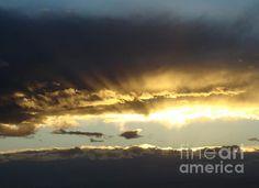 The sun peeks through the clouds after a storm. Buy prints at eva-kato.artistwebsites.com