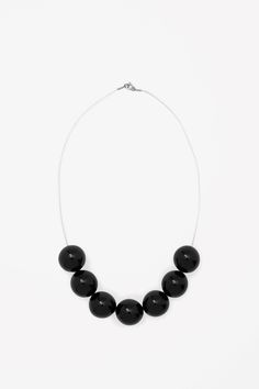 This necklace has shiny glass beads set on a clear plastic thread. It is secured with a spring clasp fastening.