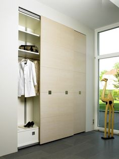 Light, natural wood closet doors enhanced with interesting hardware that is further used on the drawer at its base. Wood Closet Doors, Modern Closet Doors, Wardrobe Closet, Walk In Closet, Portland House, Minimalist Closet, Cleaning Closet, Contemporary Bedroom, Home Bedroom
