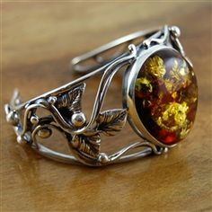 Warm, noble, highly desired Baltic Amber is displayed in an ornate handcrafted silver cuff bracelet. This amber is full of inclusions that catch the light and stimulate the imagination. A one of a kind piece that will become a family heirloom and is sure to be a favorite the moment you set your eyes upon it. #amber #fashionjewelry