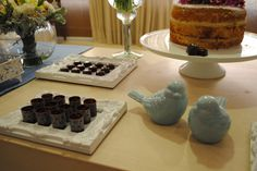 detalhe de mesa do bolo de casamento vintage romântico na cor do ano da pantone de 2016: serenity blue. Casal de passarinhos azuis e docinhos em bandejas brancas.