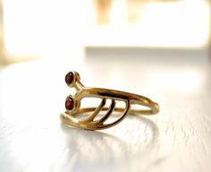 Animal snail inspired Ring Made from 14 Karat Gold filled and set with 2 Fine Facet Indian Garnets.  I got the inspiration for this piece while laying in a field near my home when suddenly i noticed a large and charismatic slug relaxing in the afternoon sun on a leaf near me. The angle he was in and the way the sun glistened of his Shell i decided to dedicate a jewel for him in Etsy for all the world to see! He really was a nice slug!