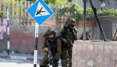 Israeli soldiers take up a position during clashes with Palestinians following a protest against Jewish settlements, in Jalazone refugee camp, near the West Bank city of Ramallah, June 12, 2015.