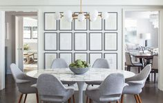 Gorgeous dining room boasts an oval brass and marble dining table lined with white and black French dining chairs placed before a wall accented with decorative trim. Mesa Saarinen Oval, Dining Room Inspiration, Architectural Digest, Dining Room Design, Decor Interior Design, Decoration, Dining Table, Knoll Table, Dining Area
