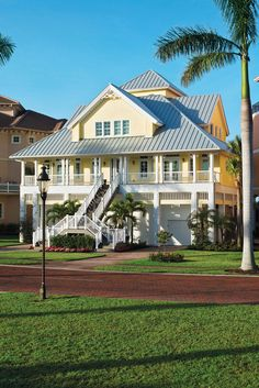 A metal roof with a series of peaks and points lends the home architectural character. Cozy and inviting with its facade of soothing pale-yellow tones and a quaint white wrap-around porch, this vacation home was built high to protect against hurricanes. Wall Bench, Key West Style, Barn Door Designs, Steel Railing, Fibreglass Roof, Florida Design, Leather Club Chairs, Victorian Cottage, Metal Roof