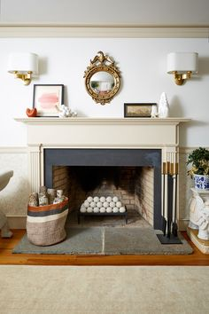 An eclectic mix of neutral, black, brick red and gilded gold decorative accents make this fireplace feel festive anytime of the year.