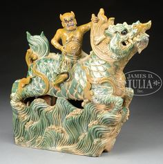 LARGE SANCAI GLAZED ROOF TILE. Ming Dynasty, China. Heavily potted with a guardian riding a mythical dragon on a sea of ocean waves. 31″ across