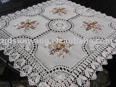 Crochet lace tablecloth.  Needlepoint decorations.