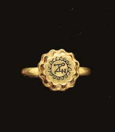 A BYZANTINE GOLD AND NIELLO ELEMENT   Circa 6th-7th Century A.D.   With rounded flutes along the tapering sides, the upper surface with a monogram encircled by a wave pattern in niello; mounted as a ring in a modern gold setting  5/16 in. (.8 cm.) high (element
