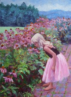 A young girl in a pink lace dress sniffs flowers alongside a brick path in the country.