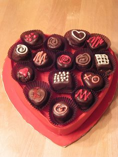 """Valentine cake with valentine """"candy"""" cupcakes on top."""