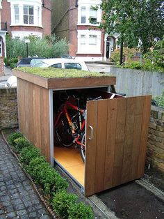 Patio with Fence, exterior stone floors, TreeSaurus Bike Storage, Outdoor bike shed, Brick wall, Raised beds, Custom storage