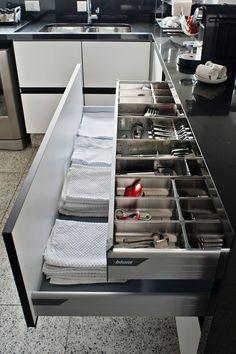 Os armários desenhados pelo escritório KTA para a cozinha do apê Moema possuem gavetas dentro degavetas: são acessórios que ajudam a separar talheres e outros utensílios e aproveitam melhor a altura do armazenador. As ferragens usadas são da Blum
