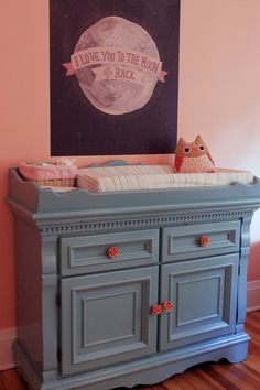 Contrasting pink knobs on a slate blue dresser in this feminine, peachy pink girl's nursery.