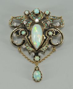 """14K yellow gold and black enamel opal and diamond pendant/brooch with center pear shaped opal surrounded by smaller opals and 13 round diamonds set in an open shield c-scroll form with opal dangle and gold chain. 2-1/4"""" L x 2-1/4"""" W. 14.8 grams."""
