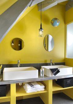 Une salle de bains sous les combles avec deux lavabos et des murs peints en jaune.