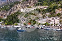 A small town on the peninsula, on a high slope with beautiful houses on a summer sunny day. On the shore of the whitewashed snow-white boats, boats and yachts.