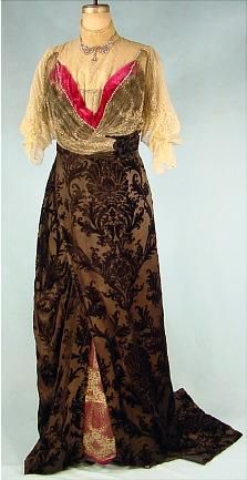 "Circa 1912 Dunlevy dark eggplant color (purplish-brown) cut velvet trained skirt which opens at lower front to reveal a splash of deep rose velvet covered in ecru lace. Bodice is mostly covered with spiderweb gold metallic and ecru lace with the overlay of low ""V"" neck velvet covered with the same laces... trimmed with rhinestones."